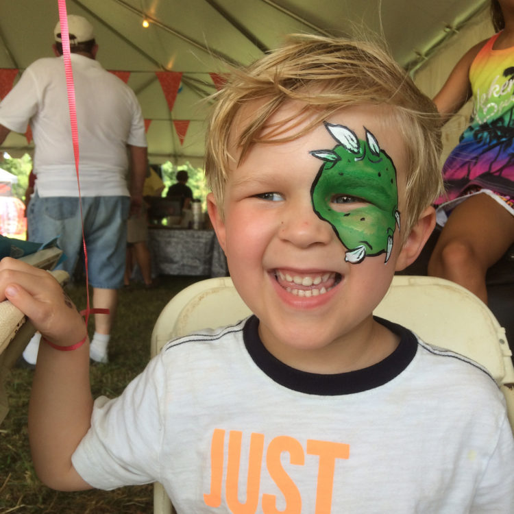 child with face painting at county fair
