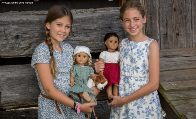 Girls holding American Girl dolls
